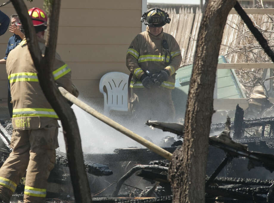 Midland firefighters contain a blaze that destroyed a trailer Wednesday, 4-15-15, in the back yard of a residence in the 1300 block of E. Pecan. Tim Fischer\Reporter-Telegram Photo: Tim Fischer