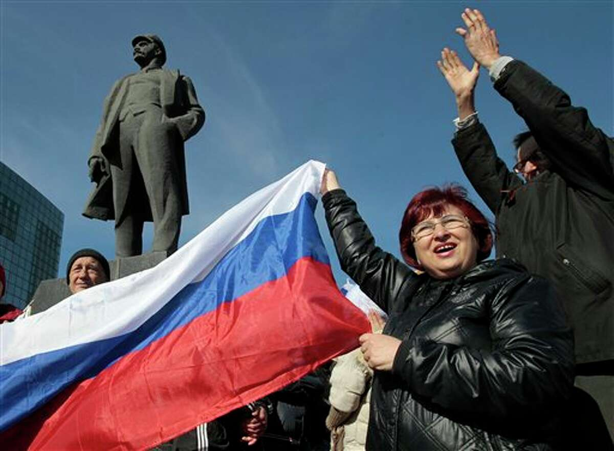 People shout slogans as they stand next to a statue of Soviet revolutionary leader Vladimir Lenin during a pro Russian rally at a central square in Donetsk, Ukraine, Saturday, March 8, 2014. Pro Russian activists continued to gather on Saturday in the eastern Ukrainian city of Donetsk, as Russia was reported to be reinforcing its military presence in Crimea. (AP Photo/Sergei Chuzavkov)