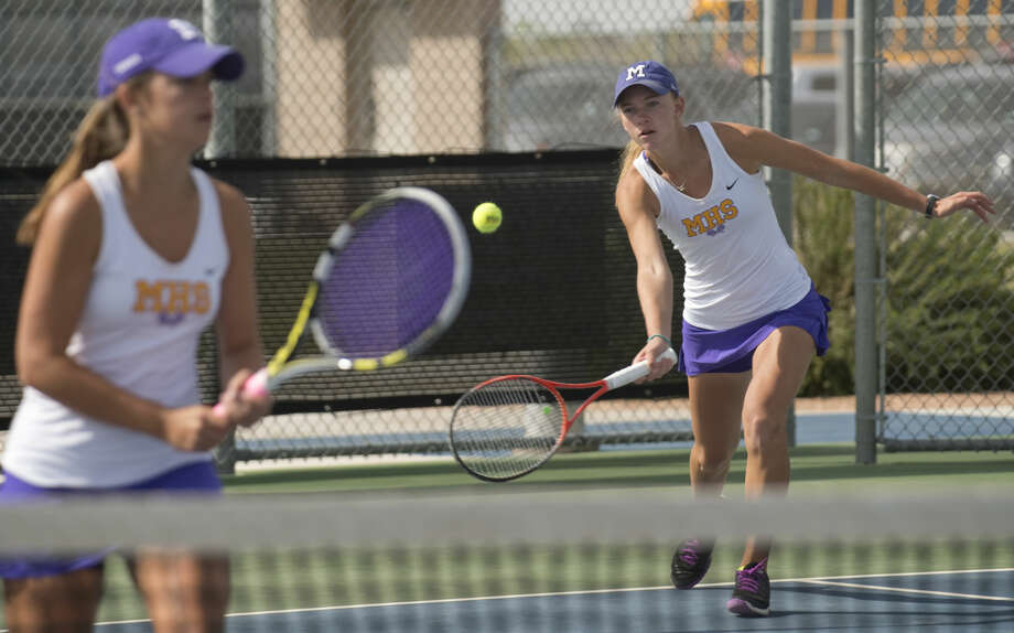 Midland High's doubles team of Allison Stewart and Kate Daugherty returns a shot Thursday 04-07-16 during a match at the Bush Tennis Center during the District 3-6A tennis championships.