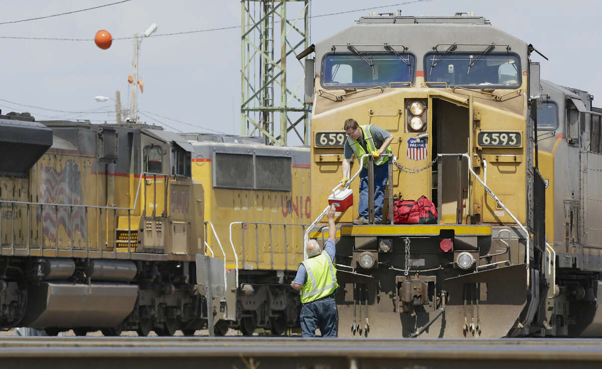 In this photo from June 6, 2014, train operators remove their belongings from a Union Pacific locomotive at a rail yard.
