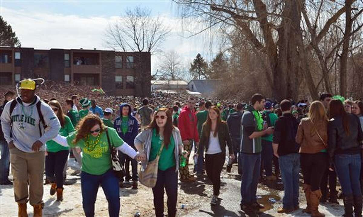 """People gather for the pre-St. Patrick's Day """"Blarney Blowout"""" near the University of Massachusetts in Amherst, Mass. on Saturday, March 8, 2014. According to the Amherst police department, four police officers were hurt as they worked to disperse hundreds of unruly students who were throwing beer cans and bottles at police on Saturday as large crowds gathered at the off-campus apartment complex. (AP Photo/The Republican, Robert Rizzuto)"""