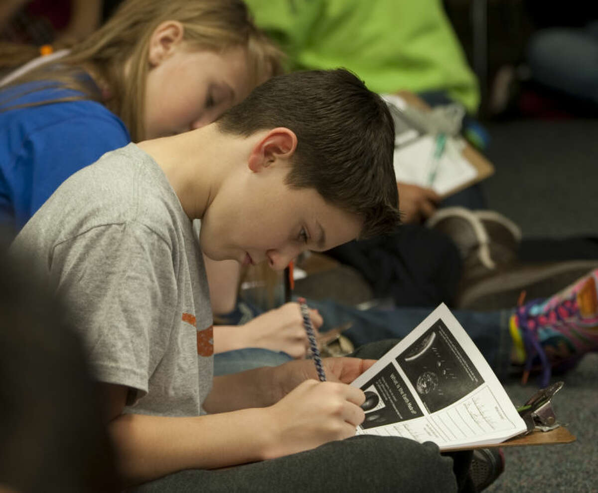 Tyler Kent and other sixth graders at Santa Rita Elementary take notes during a special science class with a working geologist as part of a partnership with MISD and West Texas Geological Society. Tim Fischer\Reporter-Telegram