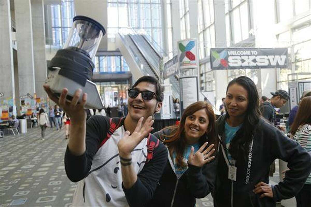 JJ Castillo, Vanessa Cottingham, and Pamela Ledbetter, left to right, wave at a Koceto Jo prototype 360° view video camera during the SXSW Interactive Festival on Saturday, March 14, 2015 in Austin, Texas. (AP Photo/Jack Plunkett)