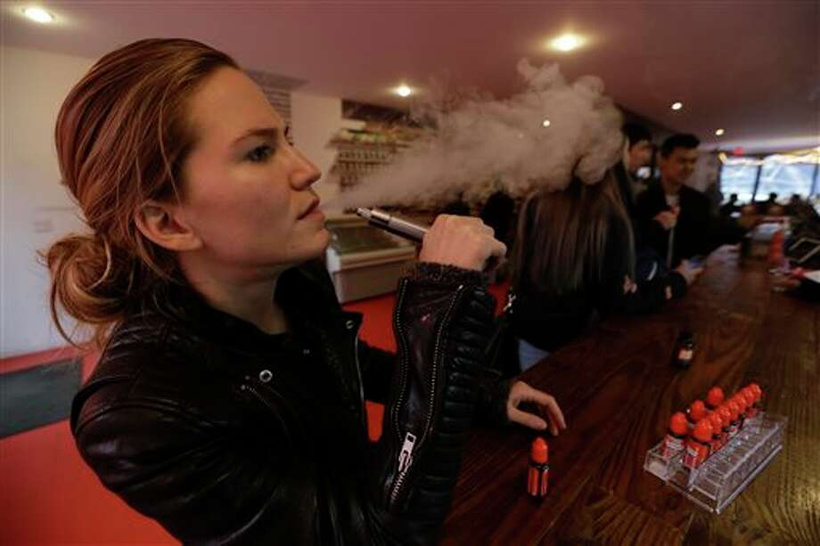 In this Feb. 20, 2014 photo, Talia Eisenberg, co-founder of the Henley Vaporium, uses her vaping device in New York. The vaporium is an intimate hipster hangout in the Soho neighborhood with overstuffed chairs, exposed brick, friendly counter help, but no booze. Instead, the proprietors are peddling e-cigarettes, along with bottles of liquid nicotine ready to be plucked from behind a wooden bar and turned into flavorful vapor for a lung hit with a kick that is intended to simulate traditional smoking. (AP Photo/Frank Franklin II) Photo: Frank Franklin II / AP