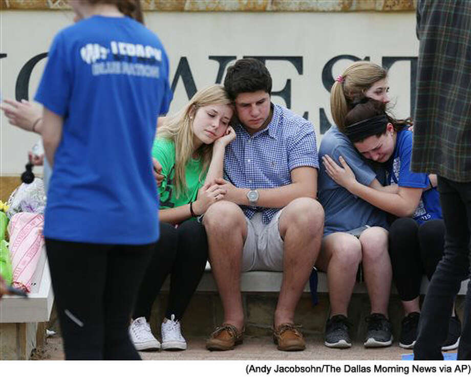 In a Friday April 8, 2016 photo, students grieve during a memorial for Plano West student Josiah Utu, 17, at Plano West High School in Plano, Texas. Josiah's brother, McCann Utu, 19, is accused of killing Josiah and their mother, Stacy Fawcett. McCann early Friday, before mortally wounding himself. (Andy Jacobsohn/The Dallas Morning News via AP) Photo: Andy Jacobsohn