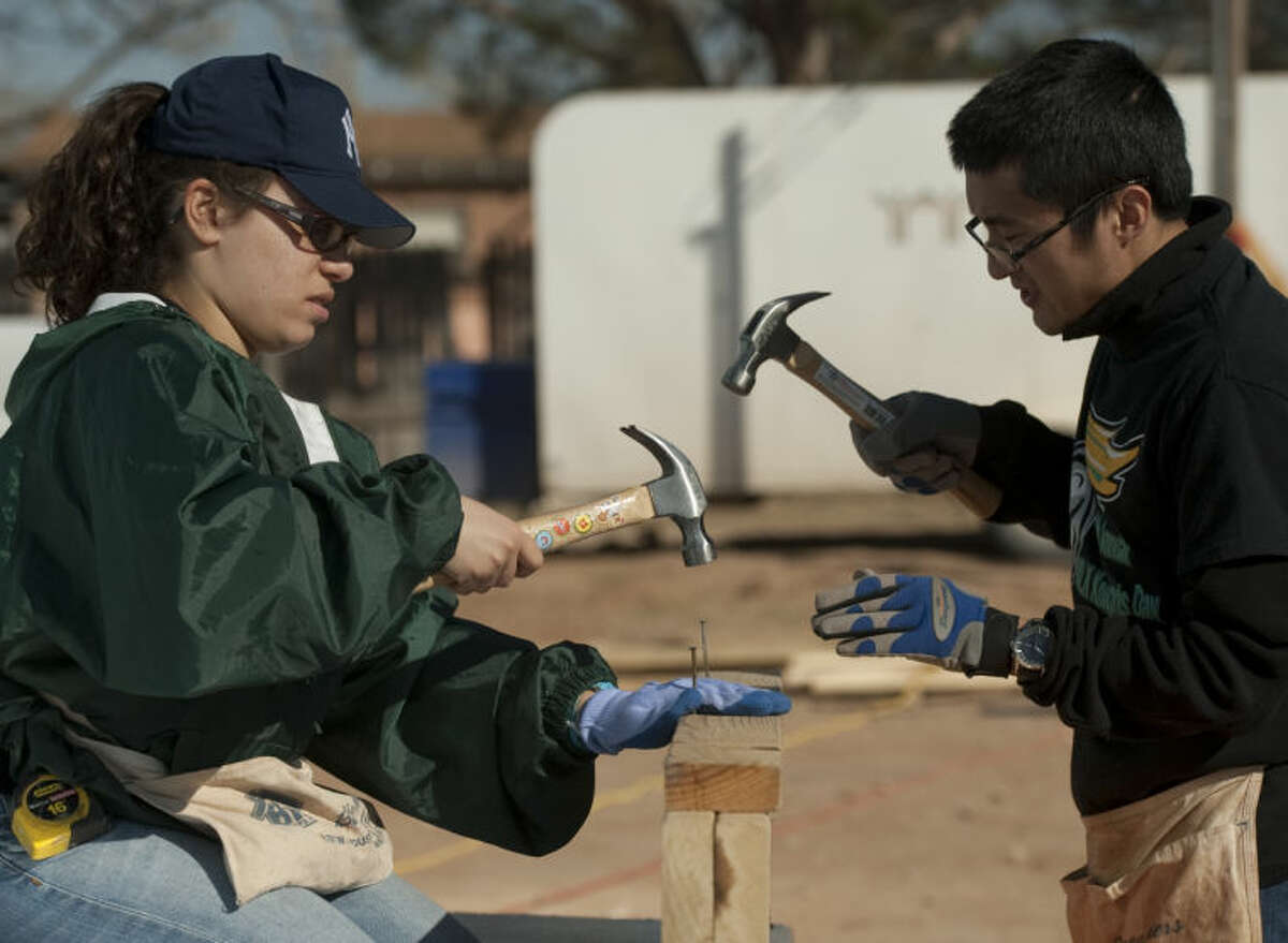 Ivette Cruz and Gan Liao nail together pieces of wood Monday as they and other students from New Jersey City University traveled to Midland for their Spring Break to participate in thge Habitat Collegiate Challenge. Tim Fischer\Reporter-Telegram