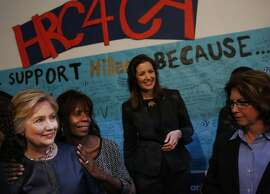 Presidential candidate Hillary Clinton poses for a photo with volunteer Darlene Tugbenyoh and another as she greets a crowd of volunteers at a surprise stop at her newly opened campaign office May 6, 2016 in downtown Oakland, Calif.