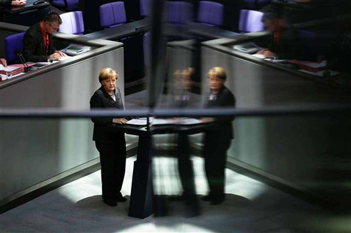 German Chancellor Angela Merkel delivers her speech, on the Ukrainian crisis at the parliament Bundestag in Berlin, Thursday, March 13, 2014. Reflections caused by glass pains of the visitors' tribune. German Chancellor Angela Merkel warned Moscow on Thursday that if it continues its current course in the Ukraine crisis, Russia risks