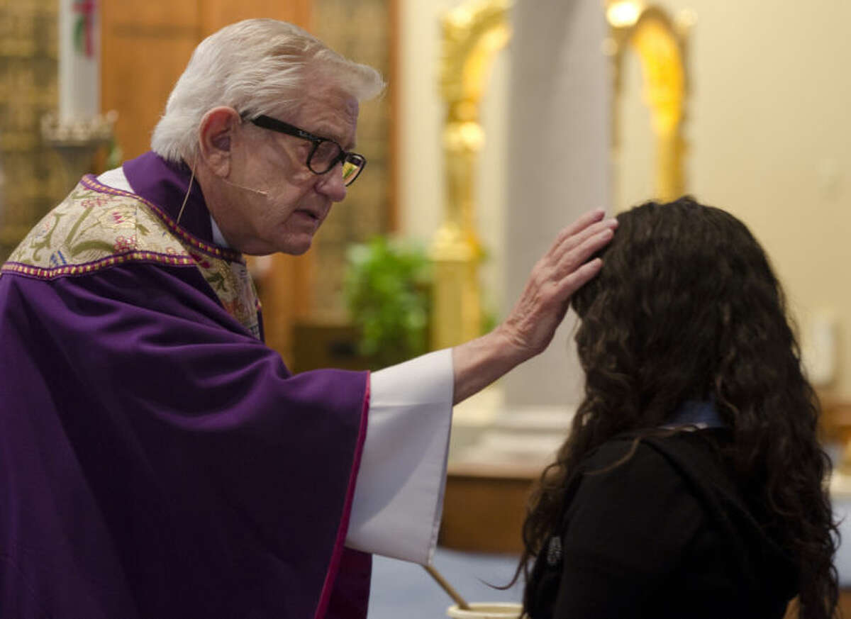 Monsignor James Bridges places ashes on parishioners heads on Ash Wednesday 2013 during early mass at St. Stephens Catholic Church. Tim Fischer\Reporter-Telegram