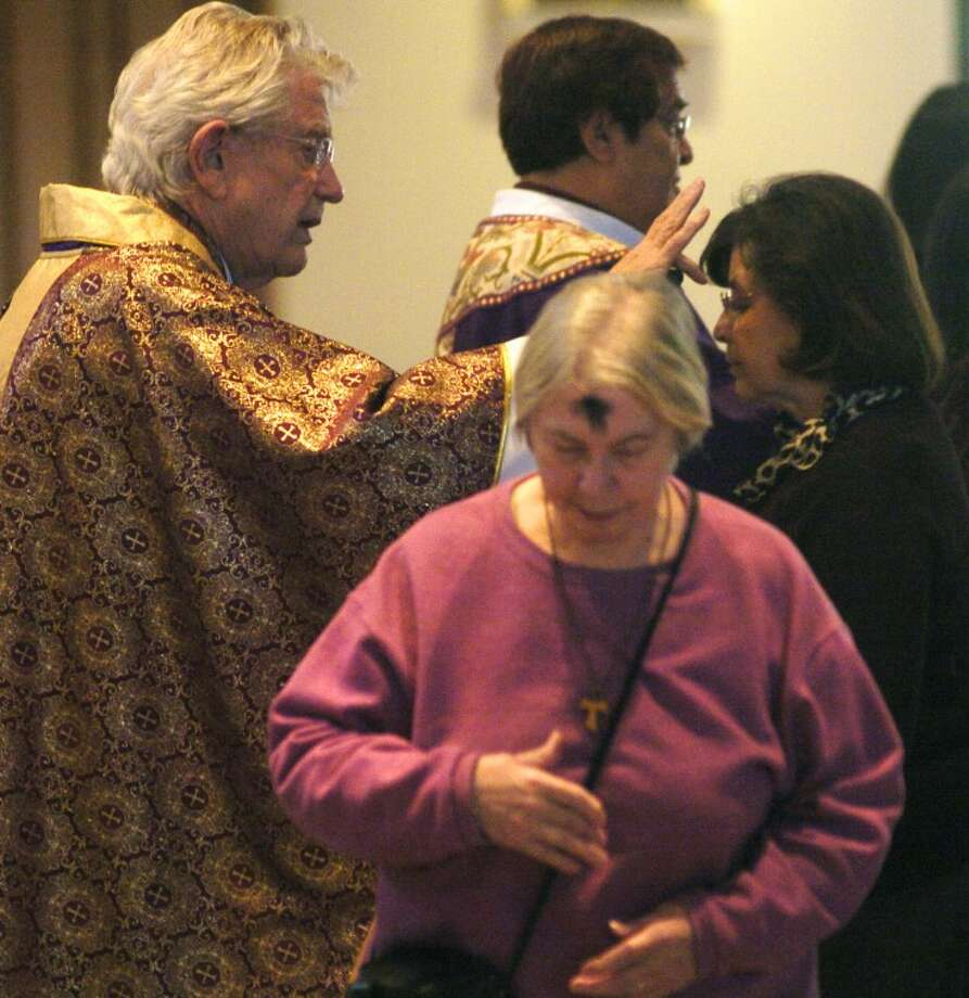 Msgr. James Bridges places ashes on parishioners foreheads on Ash Wednesday 2012 at St. Stephens Catholic Church. MRT file photo by Tim Fischer Photo: Midland