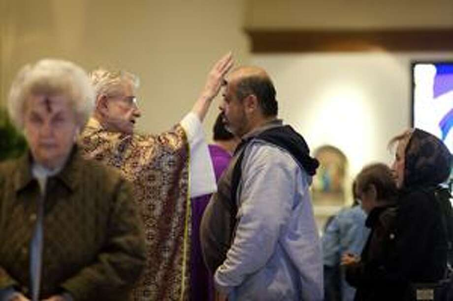 Rev. James Bridges of St. Stephens Catholic Church blesses a congregation member on the forehead with ashes during an Ash Wednesday mass during the lunch hour  on Feb. 17, 2010. photo by Gary Rhodes Photo: Gary A. Rhodes / Midland