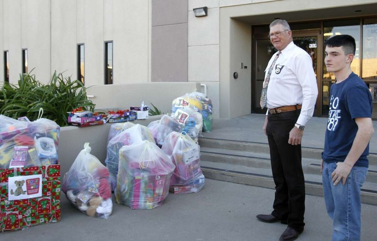 Midland County Sheriff Gary Painter and Wilson Clark stand outside the Midland County Sheriff's Office with bags of toys that Clark collected as part of the 'Toys for Cops' fundraiser. Clark partnered with Stripes convenience stores and Lee High School to collect the toys, which will be distributed by police throughout the year to children in crisis situations. James Durbin/Reporter-Telegram