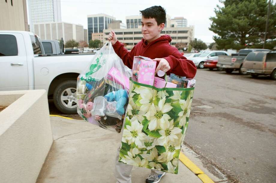 Lee Freshman High School student Wilson Clark, 15, carries bags of toys into the Midland County Sheriff's Office. Clark is a member of Education in Action, and for a community service project he collected around 200 toys from various members and organizations in the community to donate to Toys for Cops. The toys will be given to the department's Crisis Intervention Unit and to the families who lost a loved one as a result of a homicide. Cindeka Nealy/Reporter-Telegram Photo: Cindeka Nealy