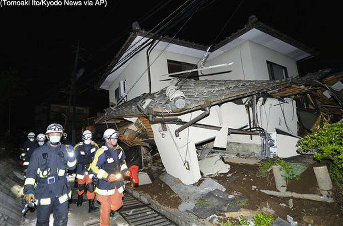 Firefighters check the damage of the collapsed house in Mashiki, near Kumamoto city, southern Japan, after the earthquake early Friday, April 15, 2016. Rescuers in southern Japan were searching for trapped residents in at least two dozen collapsed houses after a powerful 6.5 earthquake struck Thursday evening with a force that knocked out power and water and swept people off their feet. (Tomoaki Ito/Kyodo News via AP) JAPAN OUT, MANDATORY CREDIT