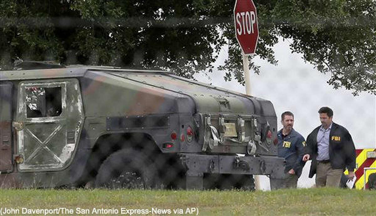 FBI officials walk behind an military vehicle near the scene of a shooting at Joint Base San Antonio-Lackland, Friday, April 8, 2016, in San Antonio. (John Davenport/The San Antonio Express-News via AP) RUMBO DE SAN ANTONIO OUT; NO SALES; MANDATORY CREDIT