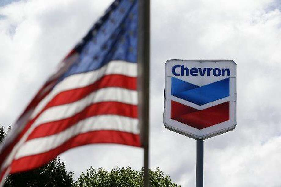 FILE - In this May 23, 2013, file photo, a United States flag flies in view of aChevrongas station in Blaine, Wash.Chevronreports quarterly earnings on Friday, Jan. 31, 2014. (AP Photo/Elaine Thompson, File)