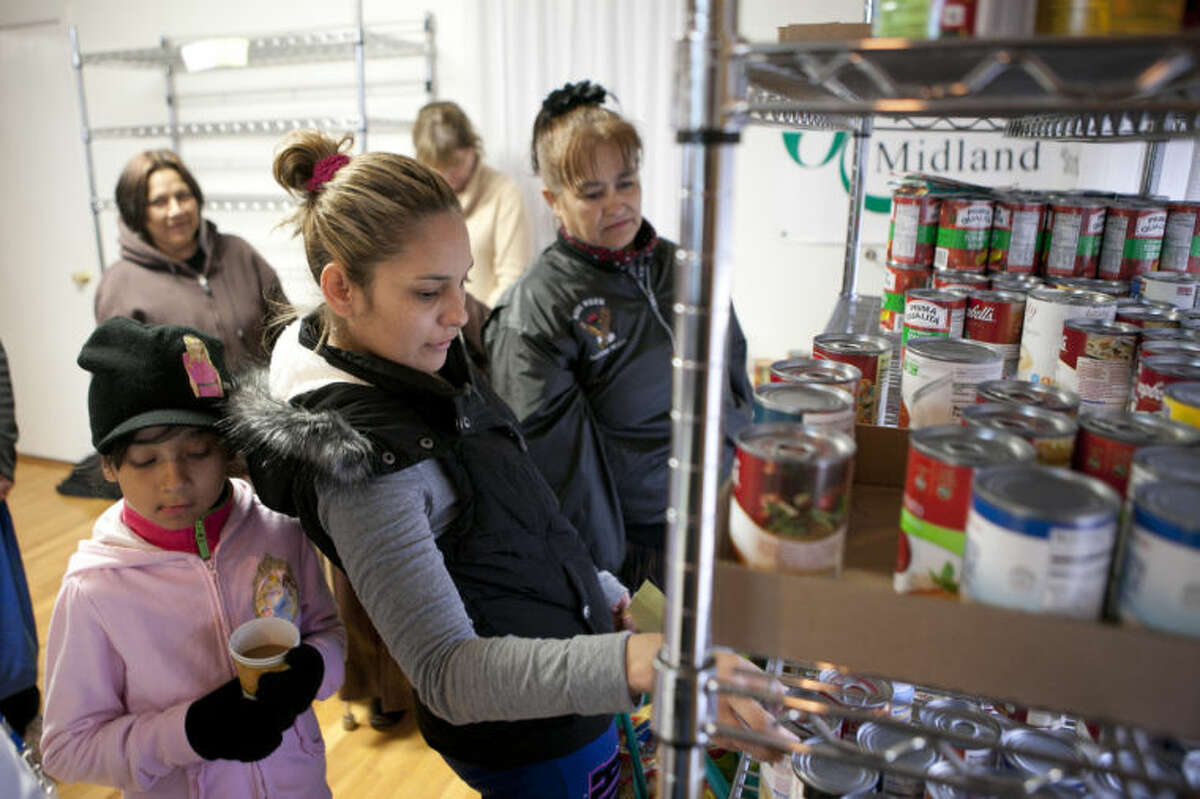 The Aguilera family gets canned goods during a November 2013 food drive at the Jubilee Center. James Durbin/Reporter-Telegram