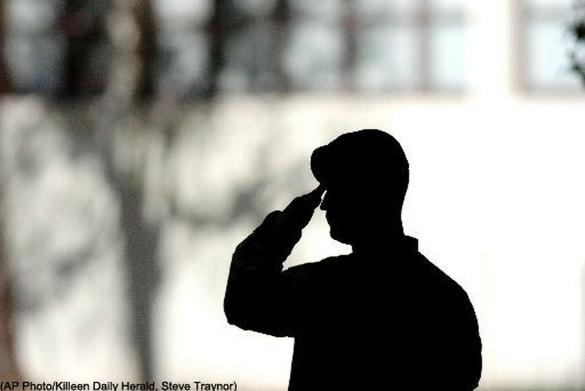 """Spc. David Hodge of the 4th Infantry Division, salutes during the playing of """"Taps"""" at a memorial service at Fort Hood, Texas, Thursday, Nov. 16, 2006. Friends, family and fellowsoldierspaid tribute to 21 divisionsoldiersthat lost their lives in Iraq during the month of October. (AP Photo/Killeen Daily Herald, Steve Traynor) ** MANDATORY CREDIT; NO SALES; MAGS OUT; TV OUT: AP MEMBERS ONLY **"""