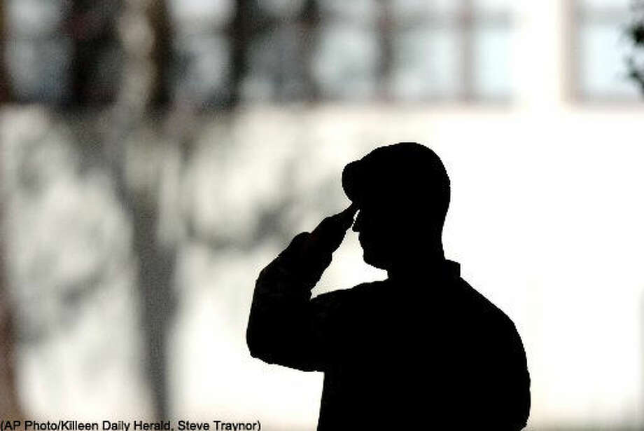 "Spc. David Hodge of the 4th Infantry Division, salutes during the playing of ""Taps"" at a memorial service at Fort Hood, Texas, Thursday, Nov. 16, 2006. Friends, family and fellow soldiers paid tribute to 21 division soldiers that lost their lives in Iraq during the month of October. (AP Photo/Killeen Daily Herald, Steve Traynor) ** MANDATORY CREDIT; NO SALES; MAGS OUT; TV OUT: AP MEMBERS ONLY **"