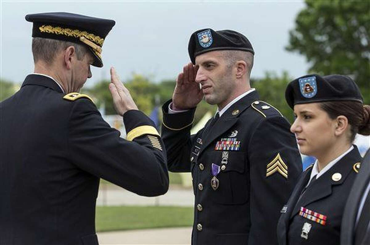 Lt. Gen. Sean B. MacFarland, left, salutes Cpl. Nathan Hewitt, center, as Sgt. Keara Torkelson, right, during a Purple Heart ceremony held at Fort Hood, Texas, on Friday, April 10, 2015. Survivors and family members of those killed during the attack by Maj. Nidal Hasan in the 2009 Fort Hood shooting were awarded 44 medals, Purple Heart for soldiers and Defense of Freedom Medals for civilians. (AP Photo/Austin American-Statesman, Rodolfo Gonzalez, Pool)