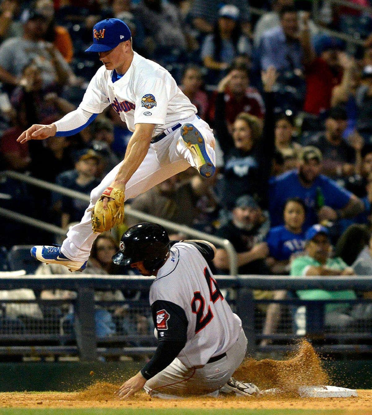 Rockhounds third baseman Matt Chapman (7) leaps over Arkansas' Eric Aguilera after tagging the base for an out during the Rockhounds season home opener Thursday, April 14, 2016 at Security Bank Ballpark. James Durbin/Reporter-Telegram
