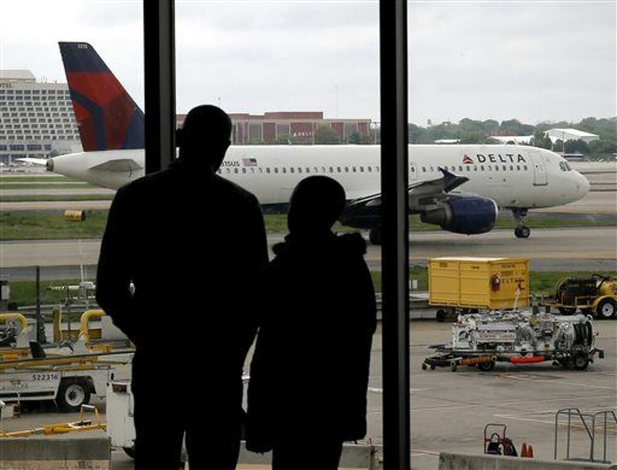 In this Tuesday, April 14, 2015 photo, travelers watch as a plane taxis at Hartsfield-Jackson Atlanta International Airport in Atlanta. After years of steadily-rising airfare, travelers this summer can expect a tiny bit of relief, a really tiny bit. The average roundtrip domestic ticket this summer now stands at $454, down $2.01 from last summer. Vacationers to Europe will fare better with tickets down 3 percent to $1,619, about $50 less. (AP Photo/Charles Rex Arbogast)