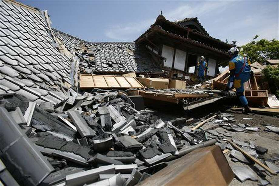 Police rescue team members search through damaged houses to check possibility of trapped people in Mashiki, Kumamoto prefecture, southern Japan, Friday, April 15, 2016. Aftershocks rattled communities in southern Japan as businesses and residents got a fuller look Friday at the widespread damage from an unusually strong overnight earthquake. (AP Photo/Koji Ueda) Photo: Koji Ueda