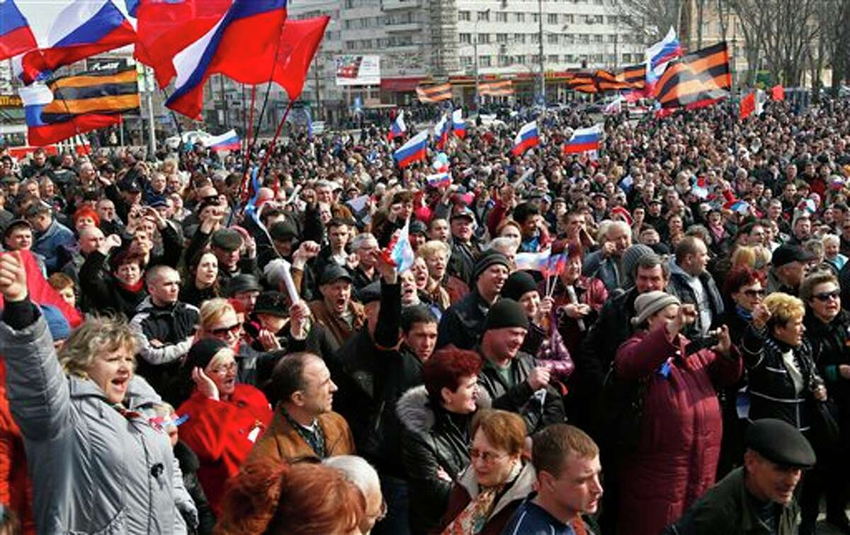 People shout slogans during a pro Russian rally at a central square in Donetsk, eastern Ukraine, Saturday, March 15, 2014. Russian forces backed by helicopter gunships and armored vehicles Saturday took control of a village near the border with Crimea on the eve of a referendum on whether the region should seek annexation by Moscow, Ukrainian officials said. (AP Photo/Sergei Grits)
