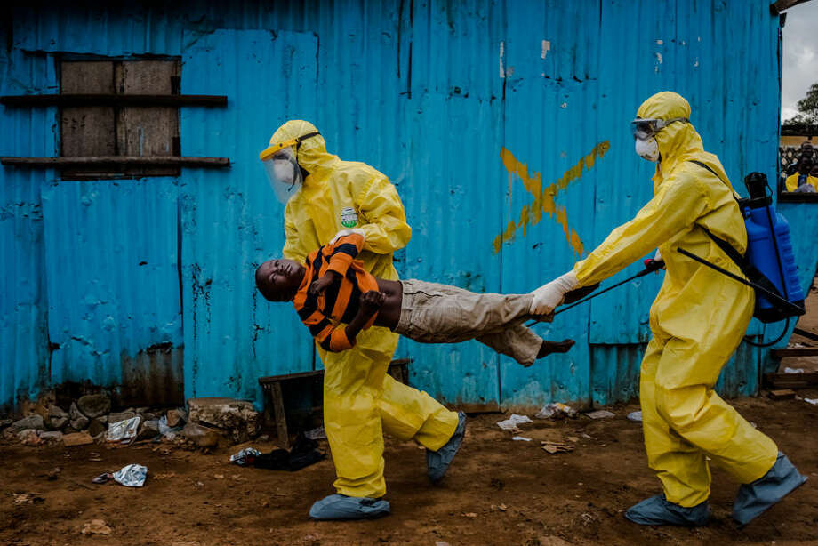 This Sept. 5, 2014, photo by New York Times photographer Daniel Berehulak, part of a winning series, shows James Dorbor, 8, suspected of being infected with Ebola, being carried by medical staff to an Ebola treatment center in Monrovia, Liberia. The boy, who was brought in by his father, lay outside the center for at least six hours before being seen. Berehulak is the winner of the 2015 Pulitzer Prize for Feature Photography, announced Monday, April 20, 2015, at Columbia University in New York. (Daniel Berehulak, New York Times, Columbia University via AP) Photo: Daniel Berehulak