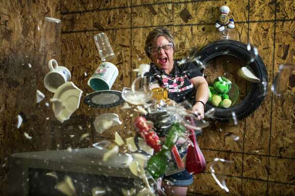 Shawn Baker uses a baseball bat to smash a stack of cups, plates and glasses at Tantrums, the business she opened after being laid off from her oil and gas job. At Tantrums, customers can rent a room full of breakable things and then trash it.