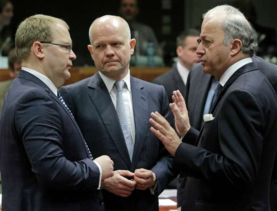 British Foreign Secretary William Hague, center, listens to French Foreign Minister Laurent Fabius, right, and Estonia's Foreign Minister Urmas Paet, left, during the EU foreign ministers council at the European Council building in Brussels, Monday, March 17, 2014. British Foreign Secretary William Hague says he is confident that the European Union will ratchet up pressure on Russia over its role in the breakaway of Ukraine's Crimea region by imposing sanctions on people linked to the secession of the peninsula. The 28-nation EU condemned the Crimea referendum which overwhelmingly backed a return to Russia, and the EU foreign ministers were assessing on Monday who to target for asset freezes and travel bans. (AP Photo/Yves Logghe) Photo: Yves Logghe / AP2014