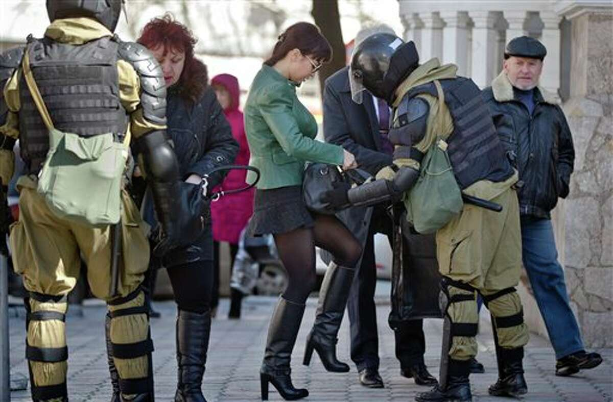 Women present their bags to armed men in riot gear, performing identity and hand bag checks on people walking near the building of Crimea's regional parliament in Simferopol, Ukraine, Monday, March 17, 2014. Crimea's parliament on Monday declared the region an independent state, after its residents voted overwhelmingly to break off from Ukraine and seek to join Russia. (AP Photo/Vadim Ghirda)