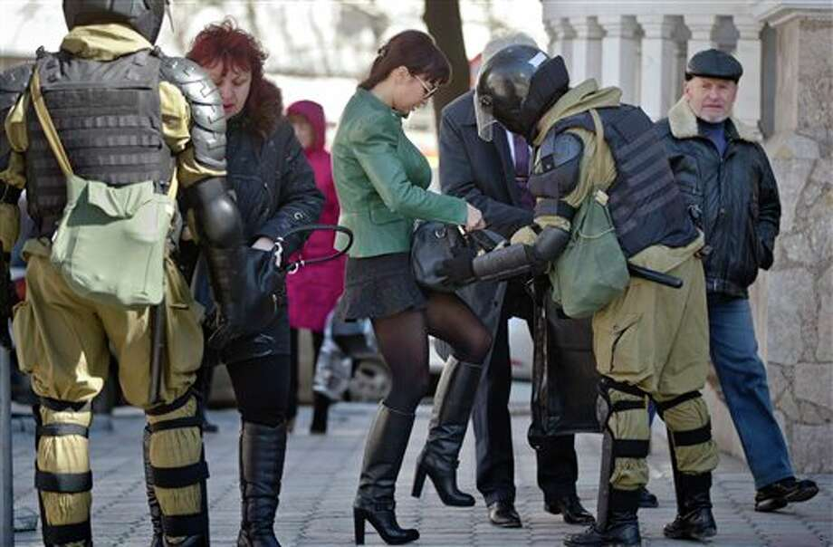 Women present their bags to armed men in riot gear, performing identity and hand bag checks on people walking near the building of Crimea's regional parliament in Simferopol, Ukraine, Monday, March 17, 2014. Crimea's parliament on Monday declared the region an independent state, after its residents voted overwhelmingly to break off from Ukraine and seek to join Russia. (AP Photo/Vadim Ghirda) Photo: Vadim Ghirda / AP