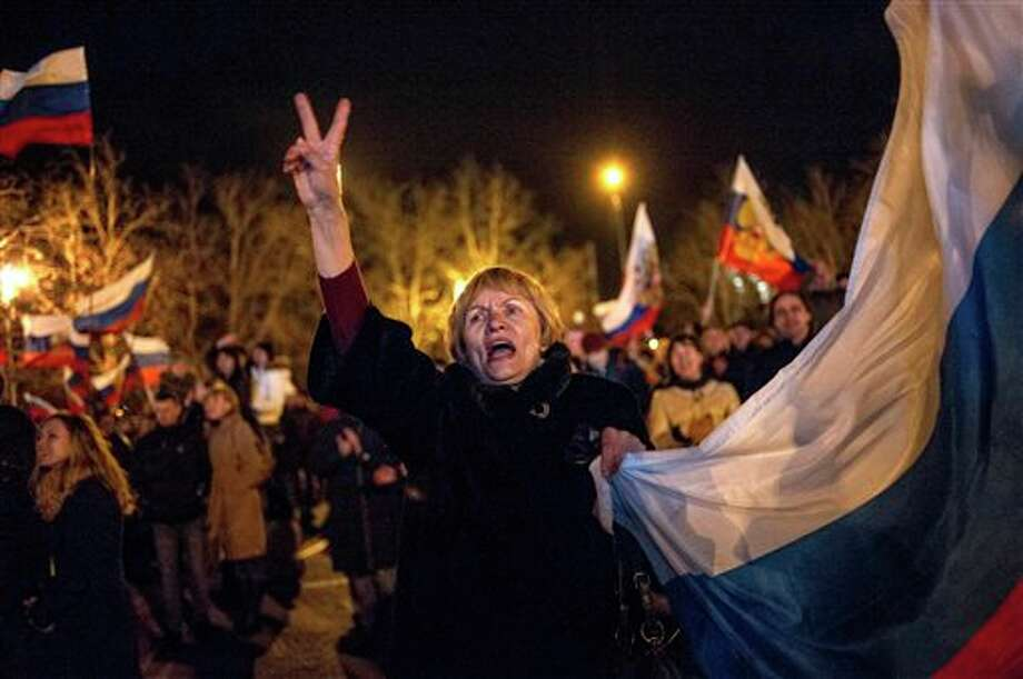 Pro-Russian people celebrate in the central square in Sevastopol, Ukraine, late Sunday, March 16, 2014. Russian flags fluttered above jubilant crowds Sunday after residents in Crimea voted overwhelmingly to secede from Ukraine and join Russia. The United States and Europe condemned the ballot as illegal and destabilizing and were expected to slap sanctions against Russia for it.(AP Photo/Andrew Lubimov) Photo: Andrew Lubimov / AP2014