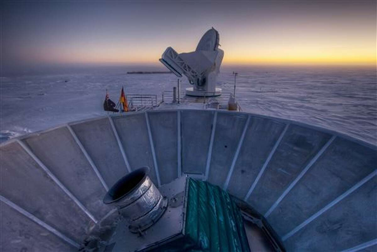In this 2007 photo provided by Steffen Richter, the sun sets behind the BICEP2 telescope, foreground, and the South Pole Telescope in Antarctica. In the faint glowing remains of the Big Bang, scientists found