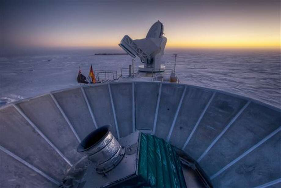 "In this 2007 photo provided by Steffen Richter, the sun sets behind the BICEP2 telescope, foreground, and the South Pole Telescope in Antarctica. In the faint glowing remains of the Big Bang, scientists found ""smoking gun"" evidence that the universe began with a split-second of astonishingly rapid growth from a seed far smaller than an atom. To find a pattern of polarization in the faint light left over from the Big Bang, astronomers scanned about 2 percent of the sky for three years with the BICEP2 at the south pole, chosen for its very dry air to aid in the observations, said the leader of the collaboration, John Kovac of Harvard. (AP Photo/Steffen Richter) Photo: Steffen Richter / VagabondPix.com"