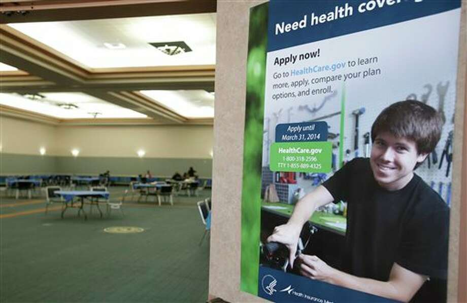 A poster touting health insurance hangs on a door to a nearly empty room at a convention center in Texas City, Texas, Saturday, March 1, 2014. Though organizers had recruited assisters to handle as many as 400 people seeking help in navigating the federal insurance marketplace, only a handful had come by in the first hours of operations. (AP Photo/Pat Sullivan) Photo: Pat Sullivan / AP