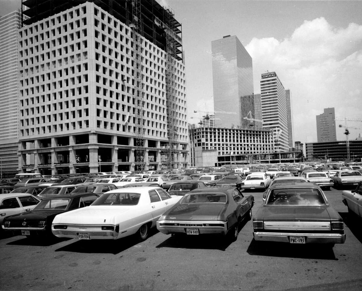 Cars packed densely in a crowded parking lot against a backdrop of heavy construction are a familiar sight in downtown Houston on June 24, 1971.