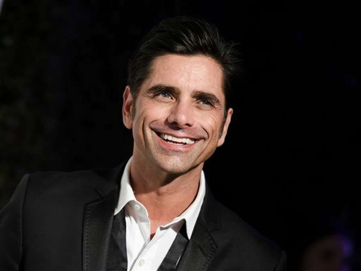 FILE - In this Feb. 22, 2015 file photo, John Stamos arrives at the 87th Academy Awards - 2015 Elton John AIDS Foundation Oscar Party in West Hollywood, Calif. Stamos says he's on board for a 13-episode reboot of the sitcom