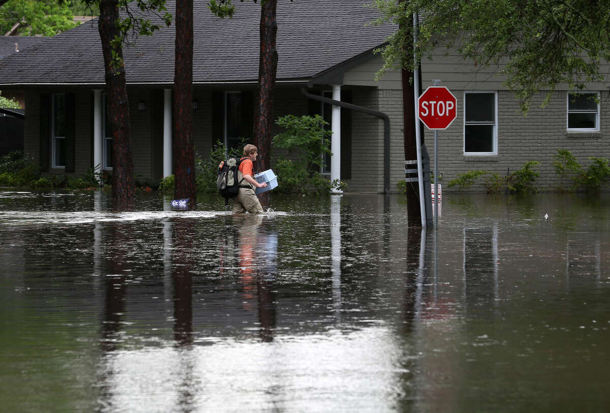 A man carries a pet carrier and other belongings through flood water, along Runnymeade Drive, in the Meyerland area, Monday, April 18, 2016, in Houston. ( Jon Shapley / Houston Chronicle )