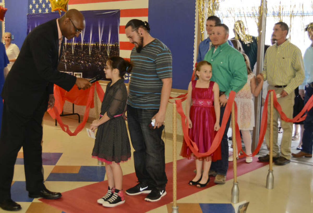 Horace Brown greets and announces Josh Garcia and his daughter, Anika, as they and other father/daughter couples enter the Daddy-Daughter Dance Thursday evening at Henderson Elementary. Tim Fischer\Reporter-Telegram