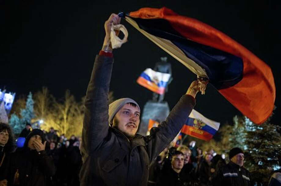 Pro-Russian people celebrate in the central square in Sevastopol, Ukraine, late Sunday, March 16, 2014. Russian flags fluttered above jubilant crowds Sunday after residents in Crimea voted overwhelmingly to secede from Ukraine and join Russia. The United States and Europe condemned the ballot as illegal and destabilizing and were expected to slap sanctions against Russia for it.(AP Photo/Andrew Lubimov) Photo: Andrew Lubimov / AP