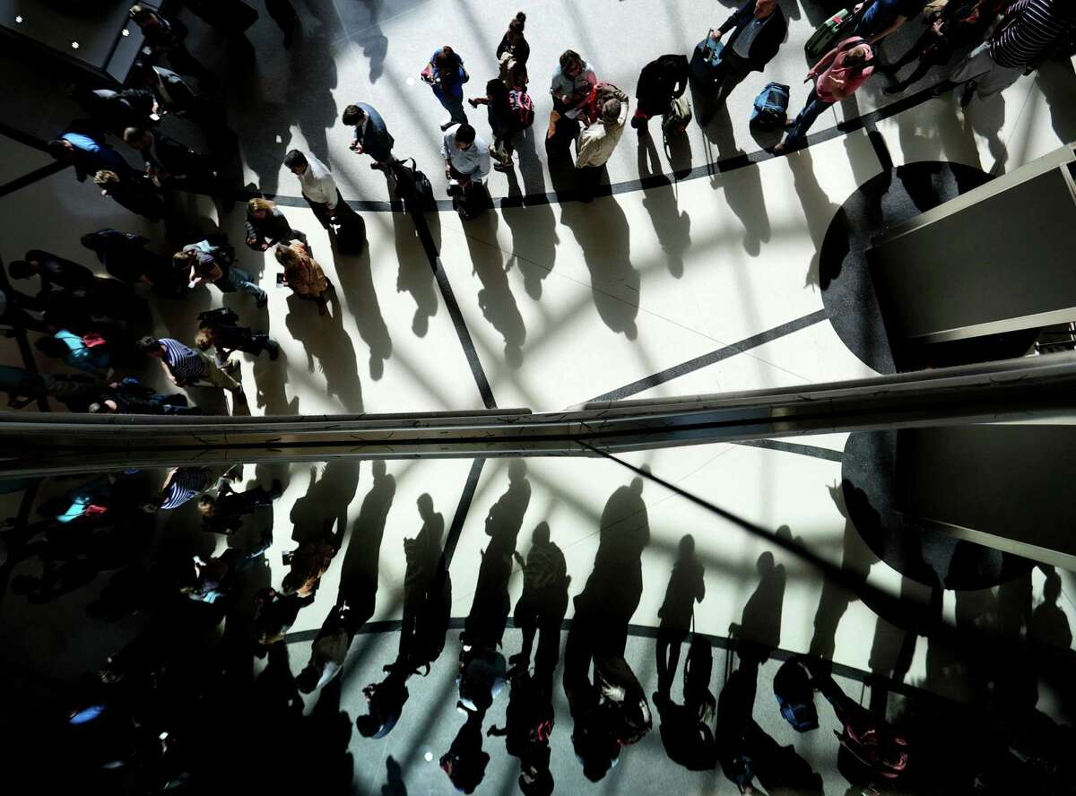 Passengers are reflected in glass as they line up to go through a security checkpoint at Hartsfield-Jackson Atlanta International Airport.