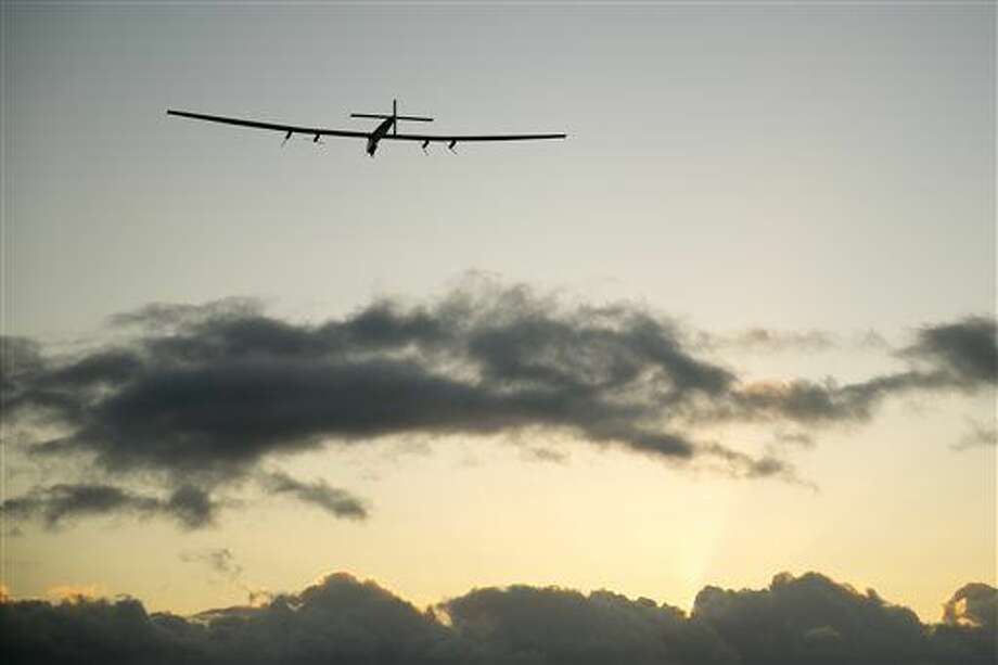 The Solar Impulse 2 solar plane flies into the sunrise out of Kalaeloa Airport, Thursday, April 21, 2016, in Kapolei, Hawaii. The solar plane will fly a two-and-a-half day journey to Northern California. (AP Photo/Marco Garcia) Photo: Marco Garcia