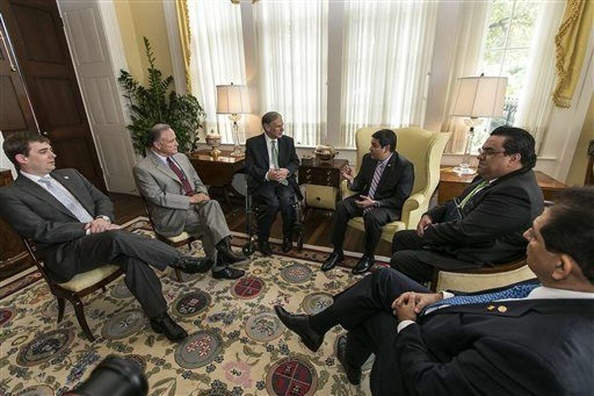Texas Governor Greg Abbott, center left, and President of Honduras Juan Orlando Hernandez, center right, visit following a meeting held at the governor's mansion in Austin, Texas, on Thursday, April 23, 2015. Looking on are staff members, Texas Governor Chief of Staff Daniel Hodge, Texas Secretary of State, Carlos Cascos, Hondoran Chancellor Arturo Corrales, and Honduran Jorge Ramon Hernandez Alcerro, Chief of Staff, left to right. (Rodolfo Gonzalez/Austin American-Statesman, Pool)