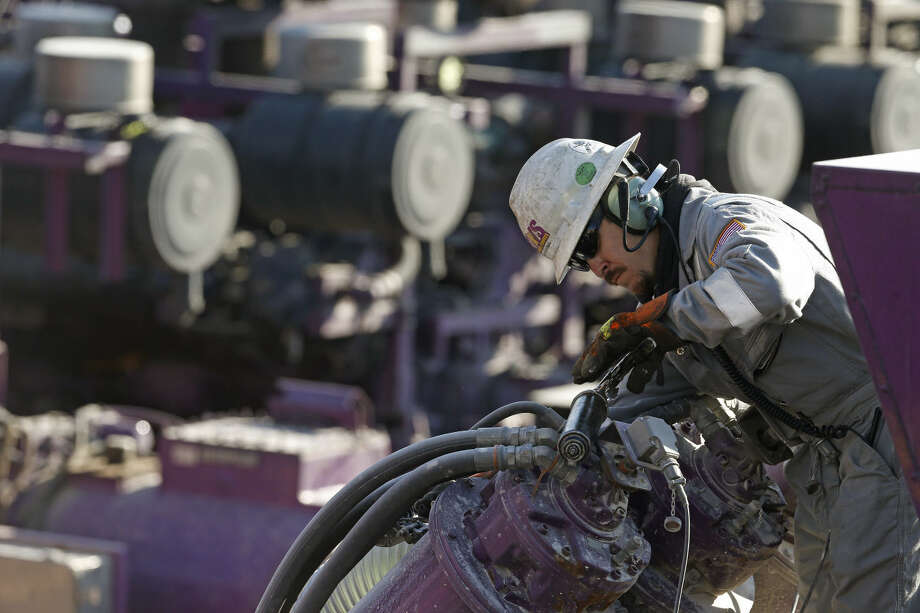 FILE - In this March 25, 2014 file photo, a worker oils a pump during a hydraulic fracturing operation at a gas and oil well pad near Mead, Colo. The University of Colorado's governing Board of Regents could vote Thursday April 16, 2015 on whether to stop investing in coal, oil and gas. The regents are expected to discuss a proposal from a student-led group called Fossil Free CU. (AP Photo/Brennan Linsley, file) Photo: Brennan Linsley