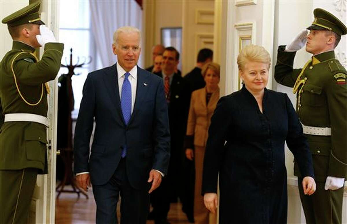 U.S. Vice President Joe Biden, left, and Lithuania's President Dalia Grybauskaite walk prior to their meeting at the Presidential palace in Vilnius, Lithuania, Wednesday, March 19, 2014. Biden arrived in Vilnius for consultations with Lithuania's President Grybauskaite and Latvia's President Andris Berzins, a few hours after Russian President Vladimir Putin approved a draft bill for the annexation of Crimea, one of a flurry of steps to formally take over the Black Sea peninsula. (AP Photo/Mindaugas Kulbis)