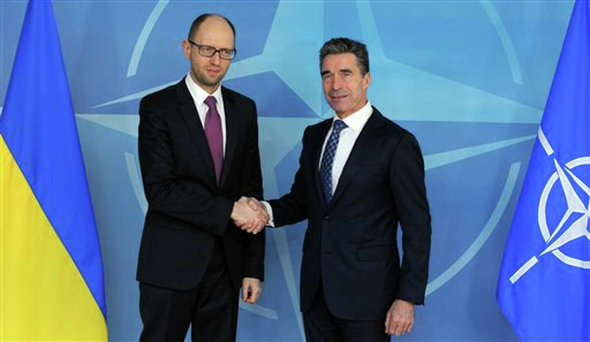 FILE - In this March 6, 2014 file photo Ukraine's Prime Minister Arseniy Yatsenyuk, left, shakes hands with NATO Secretary General Anders Fogh Rasmussen prior to a meeting at NATO headquarters in Brussels. Beyond the prize of Crimea, a picture is emerging of what Russian President Vladimir Putin ultimately wants from his power play: Broad autonomy for Ukraine's Russian-speaking regions and guarantees that Ukraine will never realize the Kremlin's worst nightmare - joining NATO. (AP Photo/Eric Vidal, File)