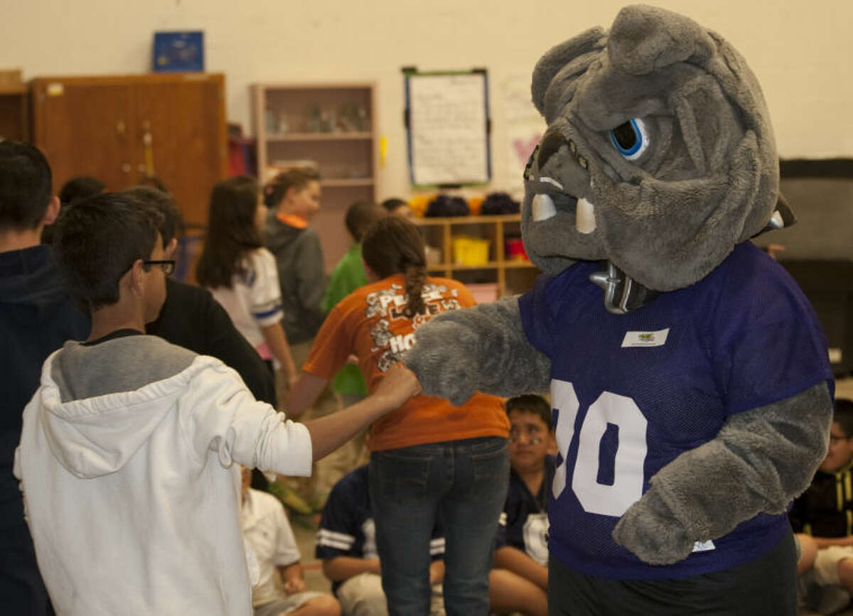Midland High mascot Spike greets students as they enter the gym during the Fuel Up to Play 60 pep rally Tuesday morning at Fannin Elemenatry. Tim Fischer\Reporter-Telegram