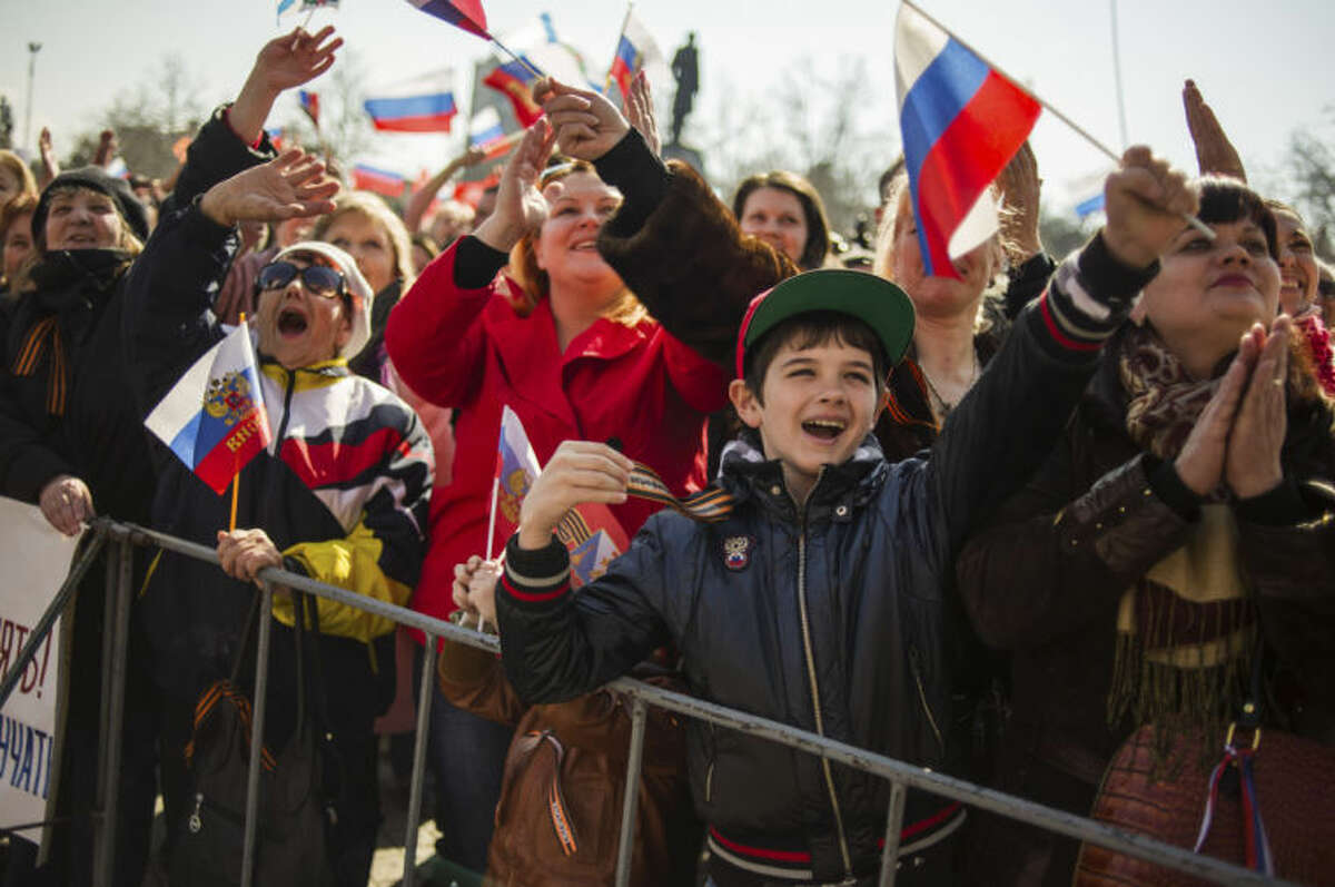 People wave Russian flags as they gather at a square to watch a televised address by Russian President Vladimir Putin to the Federation Council, in Sevastopol, Crimea, Tuesday, March 18, 2014. Putin on Tuesday fiercely defended Russia's move to annex Crimea saying Crimea's vote on Sunday to join Russia was in line with